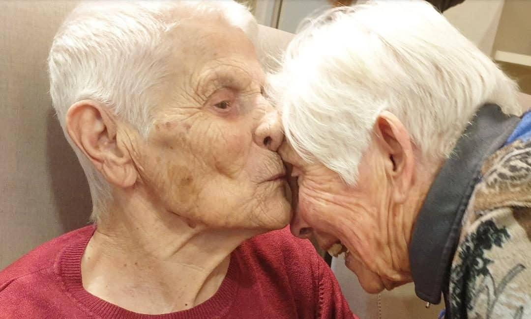 hombre mayor besa a su mujer